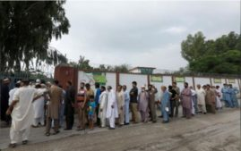 People stand in a line as they wait for a polling station to open during general election in Rawalpindi on July 25. Reuters Photo